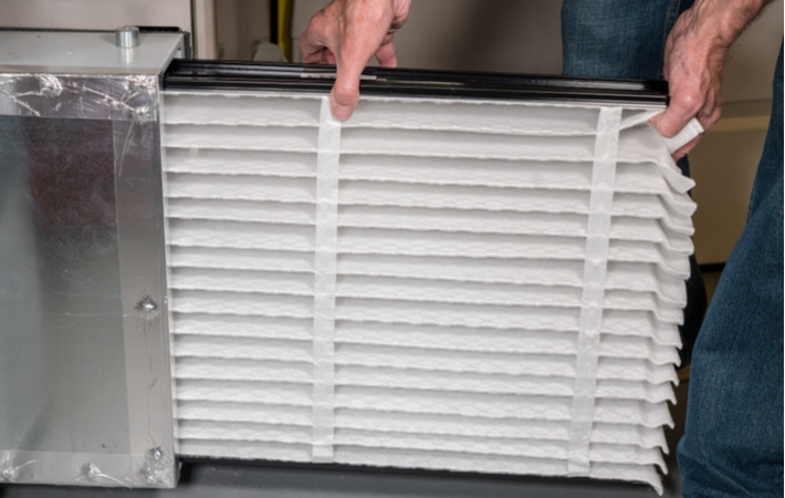A man replacing a furnace filter with a brand new, clean one