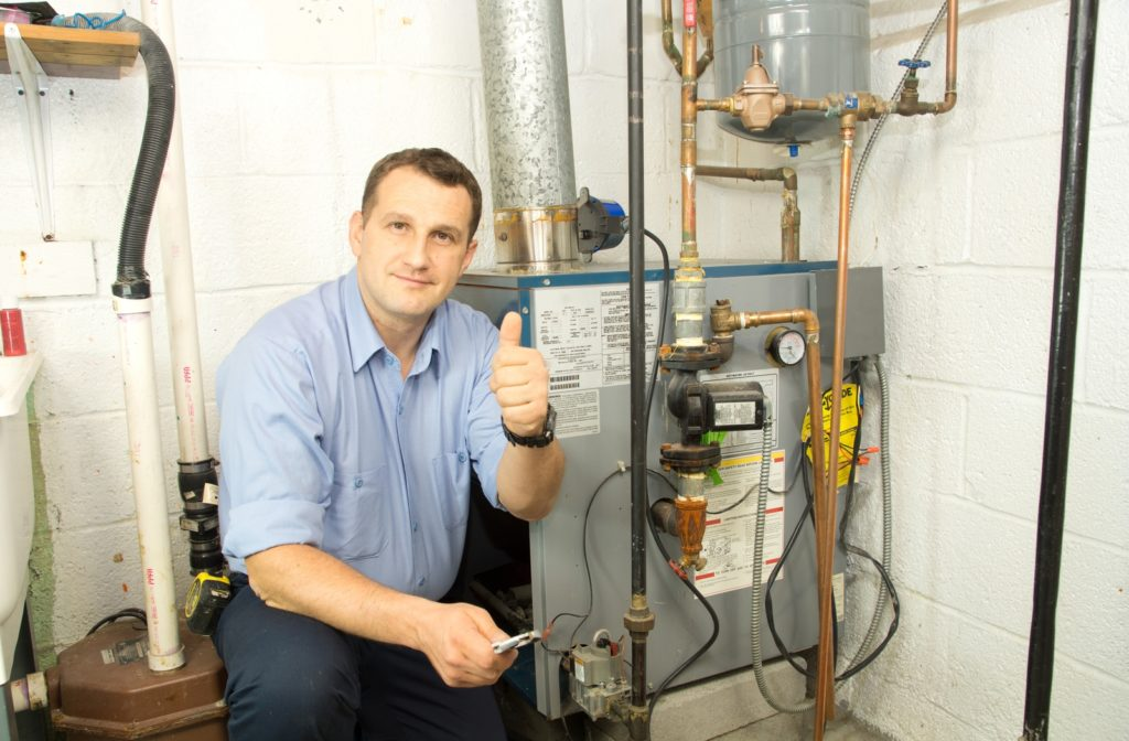 Man giving thumbs up while sitting beside furnace in basement of house