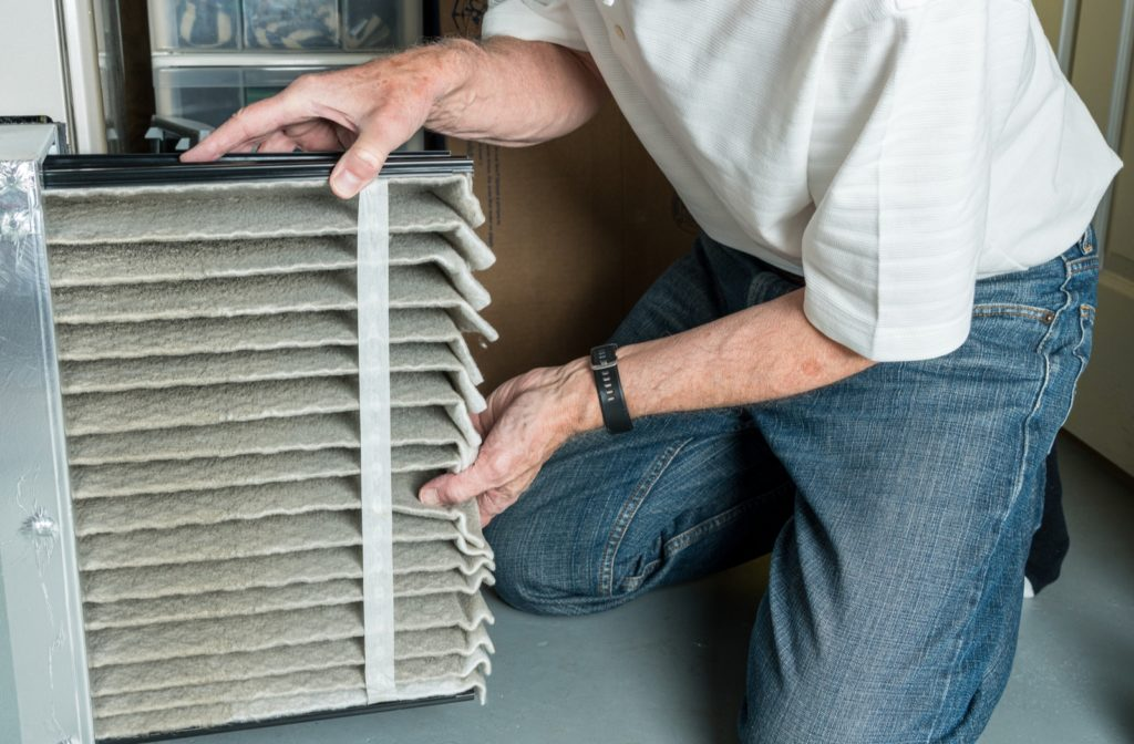 Senior man changing dirty furnace filter from furnace system in his basement.