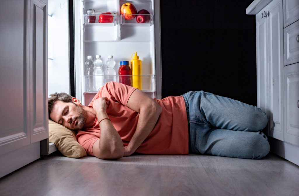Man sleeping on the floor in the kitchen in front of an open refrigerator because his house is too warm to sleep in the summer