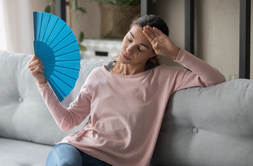 Woman sitting on her couch overheating using a paper fan to try to cool herself down because her air conditioning failed