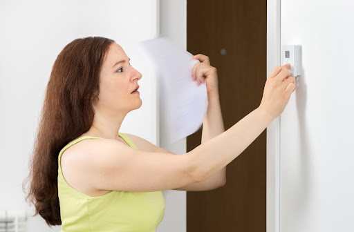 Woman suffering from heatstroke having thermostat problems when trying to turn on her AC