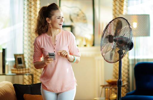 Woman smiling in front of her fan keeping cool on a hot summer day